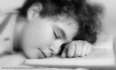Slitent barn sover på boka m kildetekst